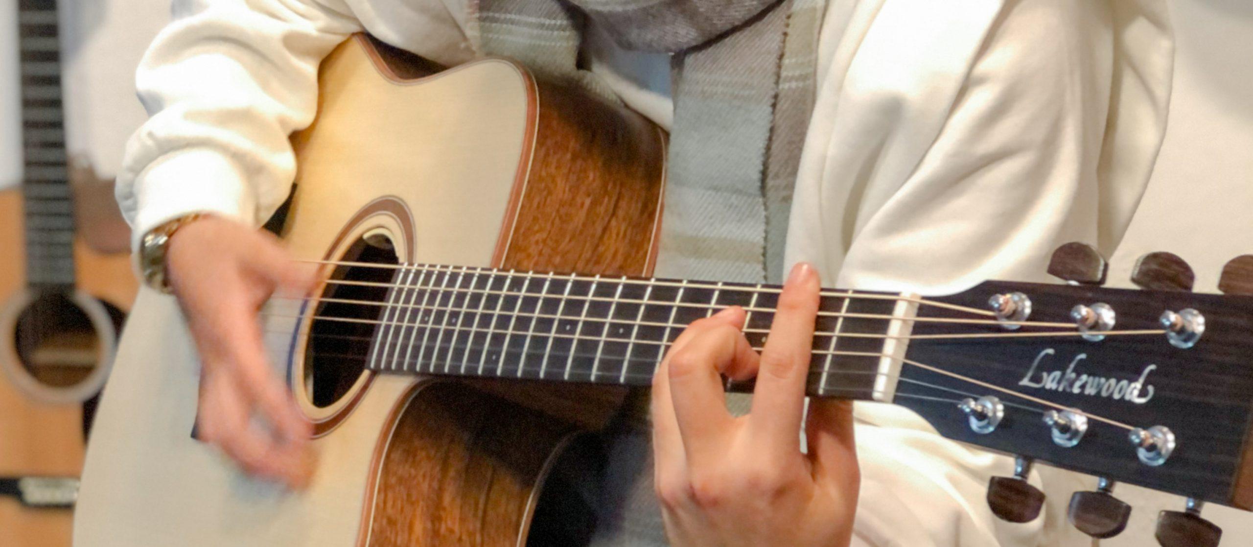 Praktikantin beim Spielen einer Westerngitarre der Marke Lakewood